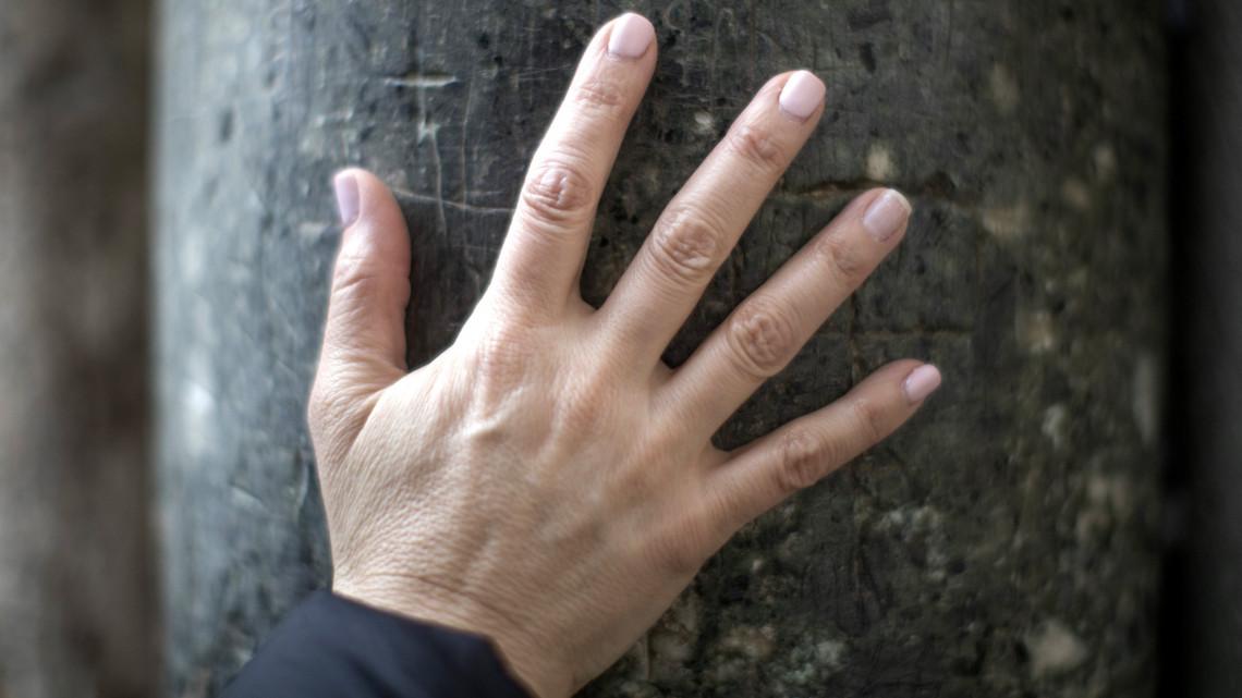 piros foltok ujjak között a kezek fotó